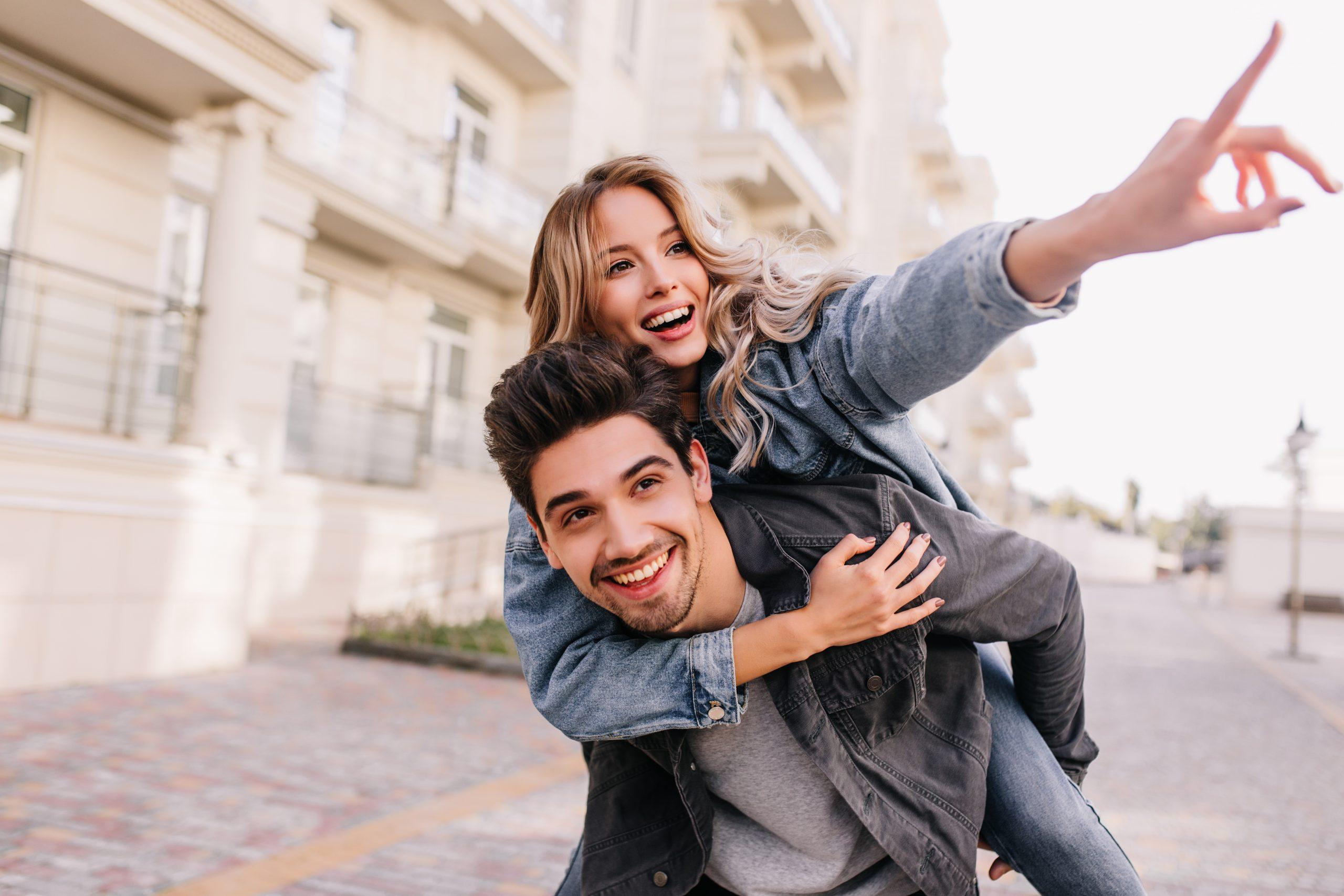 Caucasian pretty girl walking around city with boyfriend. Smiling brunette man spending weekend with girlfriend.